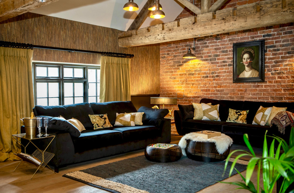 Mid-sized eclectic open concept medium tone wood floor, brown floor, vaulted ceiling and brick wall living room photo in Other with a wood stove, a metal fireplace and a wall-mounted tv
