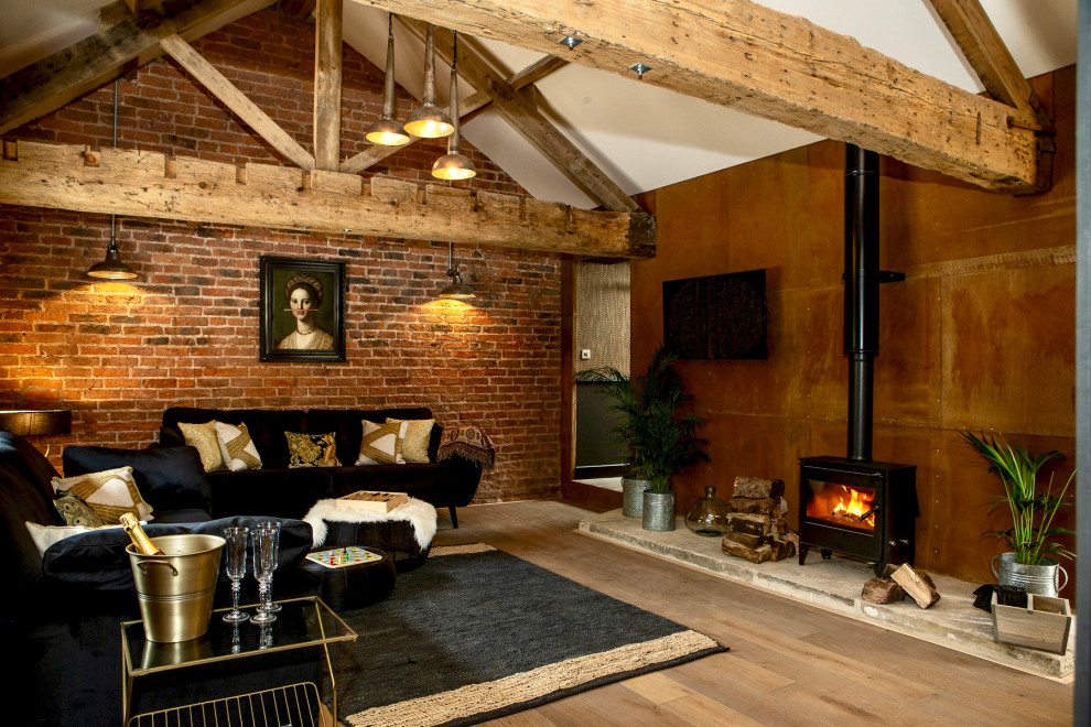 Mid-sized eclectic open concept medium tone wood floor, brown floor, vaulted ceiling and brick wall living room photo in Other with a wood stove and a wall-mounted tv