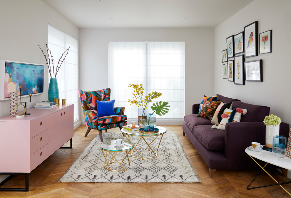 Example of a mid-sized eclectic open concept medium tone wood floor and brown floor living room design in London with white walls and no tv