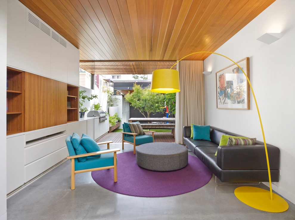 Living room - contemporary formal and open concept concrete floor living room idea in Sydney with white walls and a concealed tv