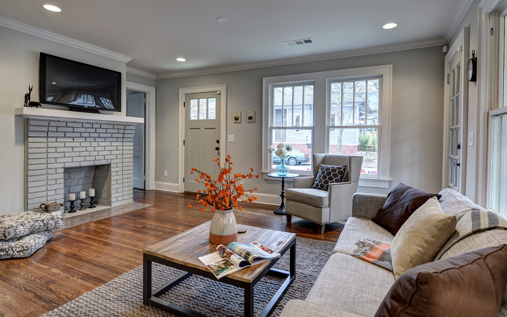 Inspiration for a small timeless open concept medium tone wood floor living room remodel in Atlanta with gray walls, a standard fireplace and a brick fireplace