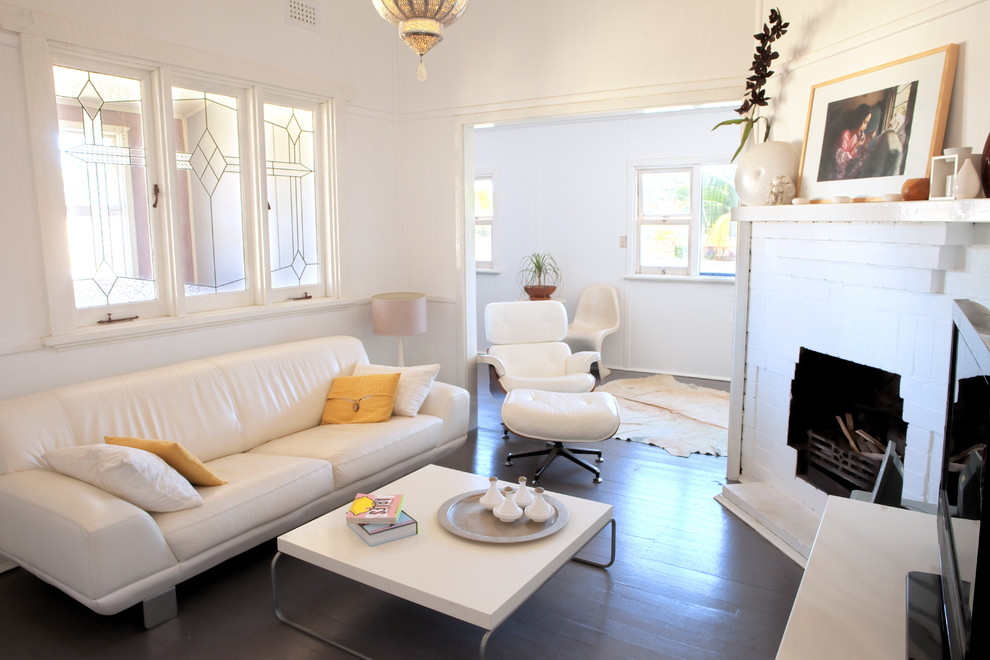 Example of a small trendy painted wood floor living room design in Perth with a corner fireplace, a brick fireplace, white walls and a tv stand