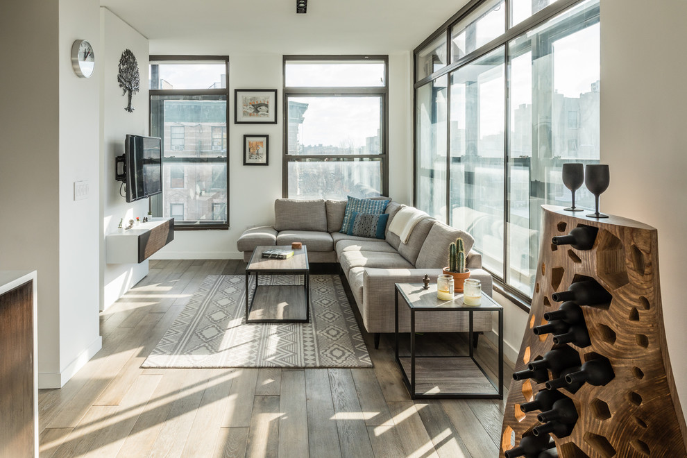 Living room - mid-sized contemporary dark wood floor and brown floor living room idea in New York with white walls and a wall-mounted tv
