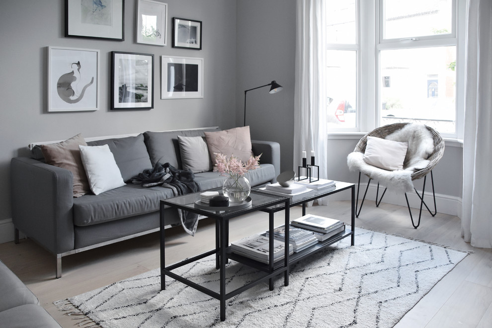 Small danish enclosed light wood floor and white floor living room photo in Hampshire with gray walls