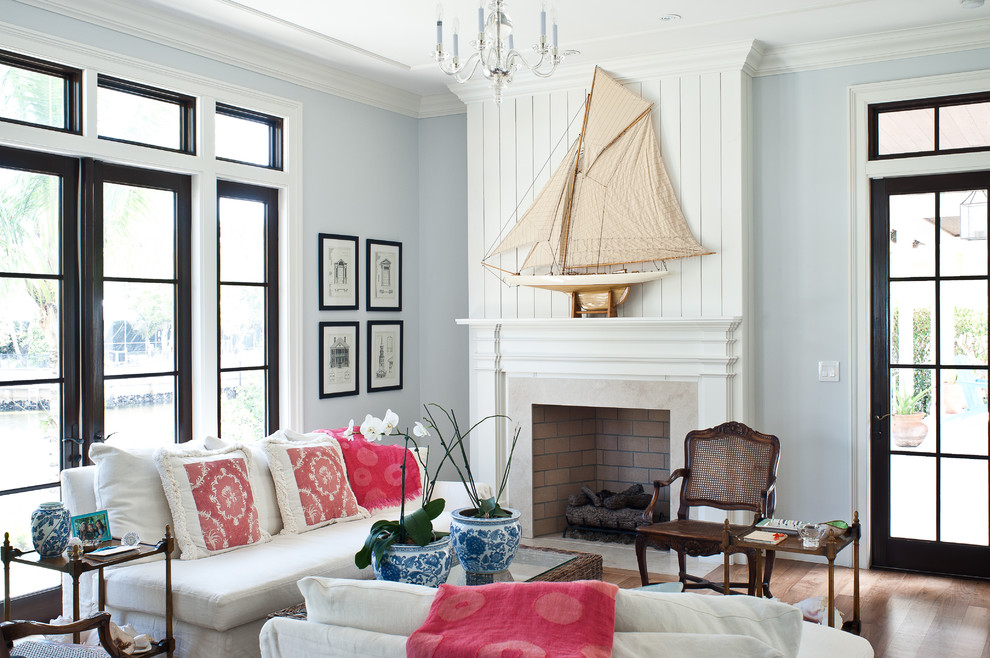 Inspiration for a tropical living room remodel in Miami with blue walls and a standard fireplace