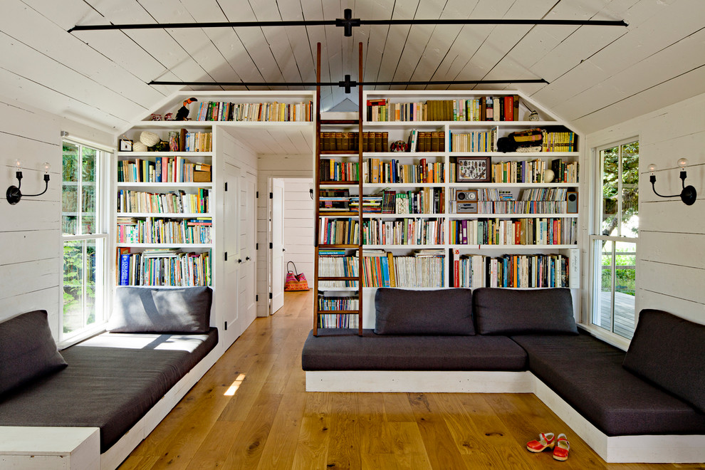 Living room library - country medium tone wood floor living room library idea in Portland with white walls