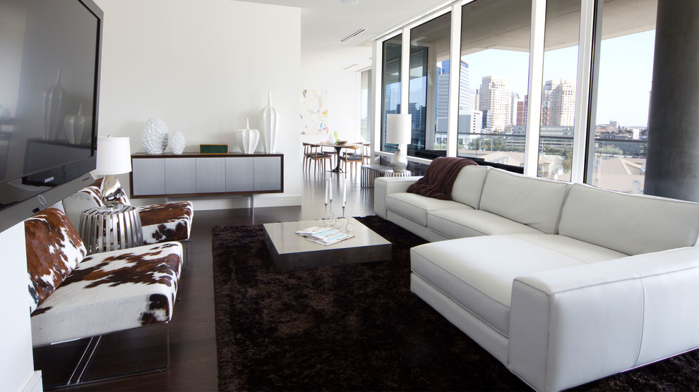 Example of a large minimalist formal and open concept dark wood floor living room design in Dallas with white walls, no fireplace and a wall-mounted tv