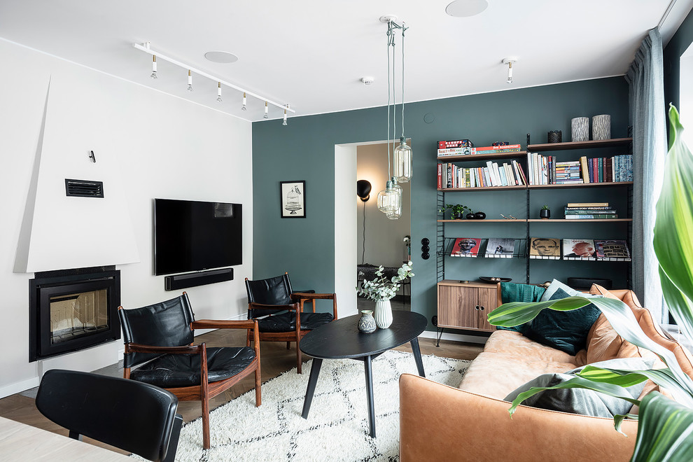 Example of a large danish open concept dark wood floor and brown floor living room design in Gothenburg with blue walls, a standard fireplace, a plaster fireplace and a wall-mounted tv