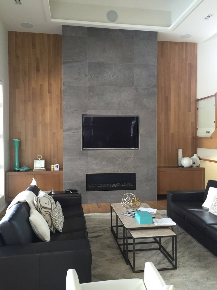 Large minimalist open concept light wood floor living room photo in Toronto with a stone fireplace and a media wall