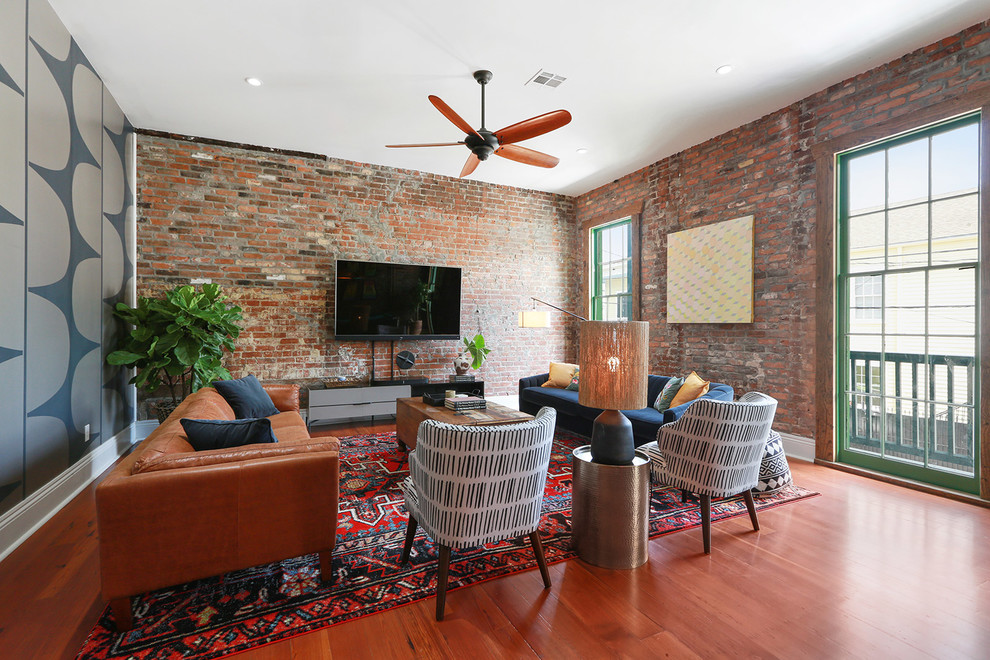Inspiration for an industrial medium tone wood floor and brown floor living room remodel in New Orleans with blue walls and a wall-mounted tv