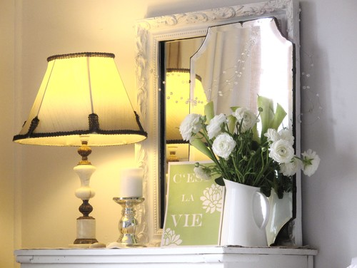 Lovely white mantel decorated with a lamp, a candle, a mirror, and a pitcher vase of white flowers