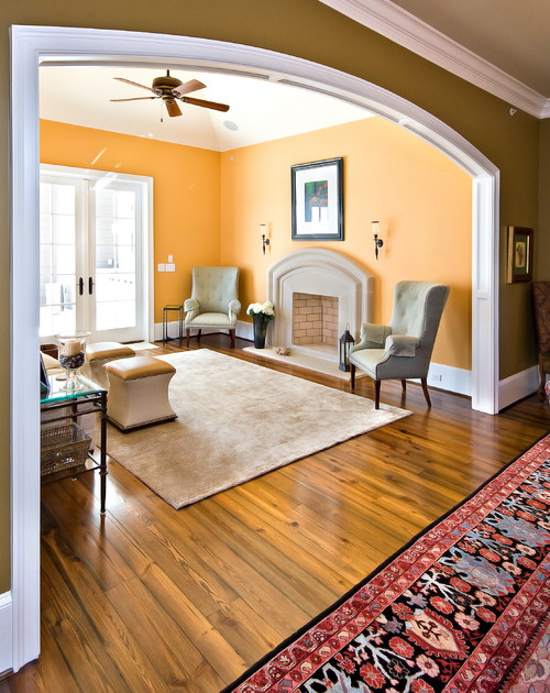 Can you share the warm yellow orange paint color of this room for Designs of arches in living room