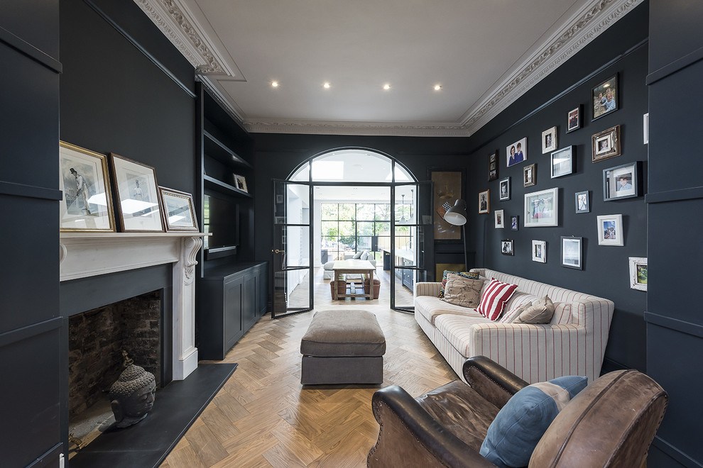Inspiration for a timeless enclosed medium tone wood floor living room remodel in London with black walls and a standard fireplace