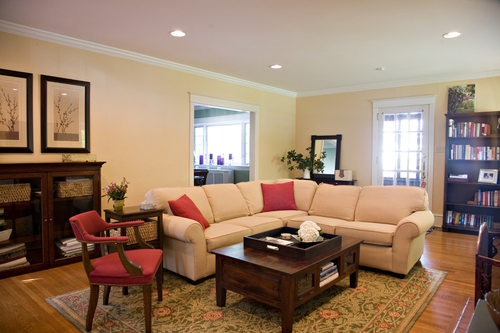 traditional living room with cream sectional and red