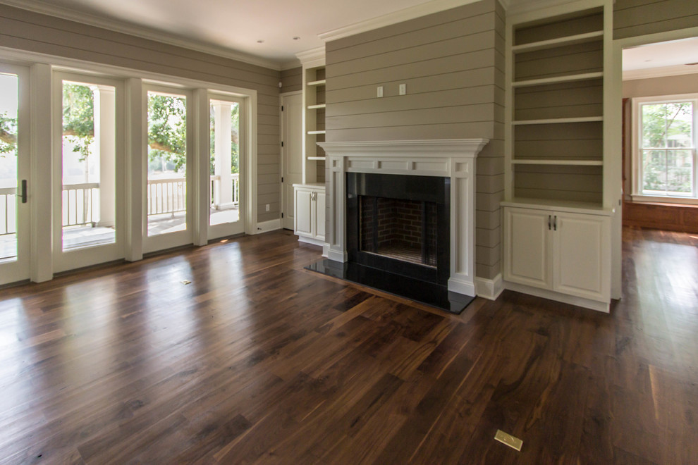Example of a classic open concept and formal dark wood floor living room design in Charleston with beige walls, a standard fireplace and a wood fireplace surround