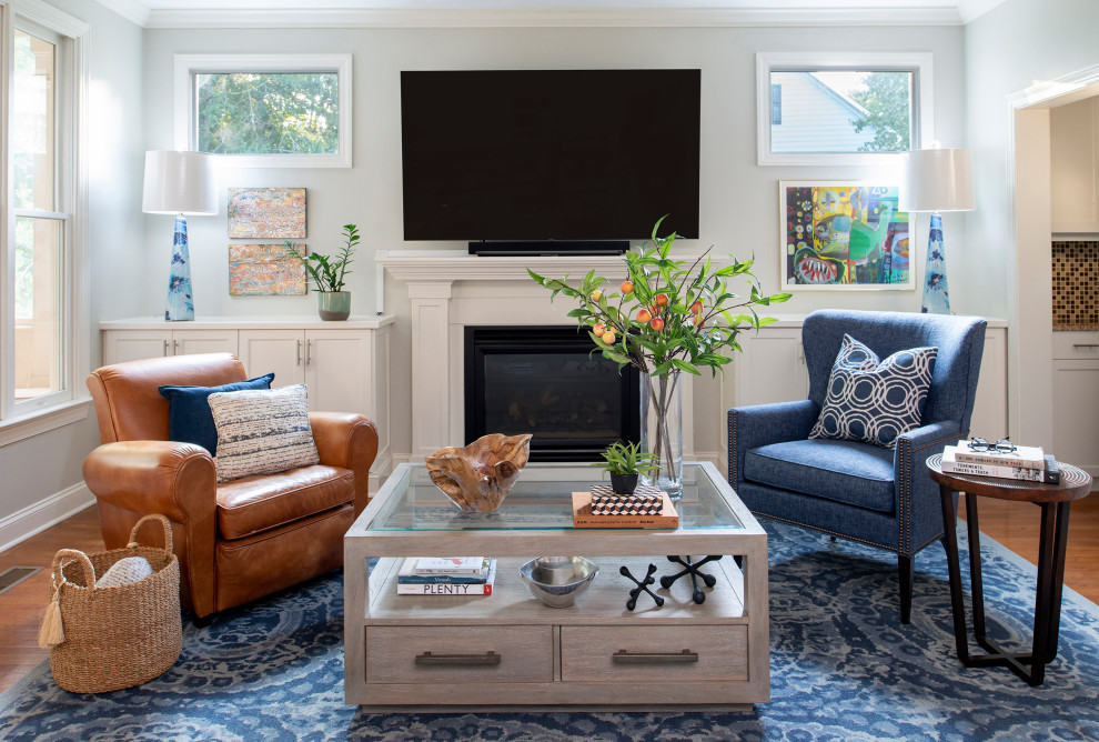 Mid-sized transitional open concept medium tone wood floor and brown floor living room photo in Raleigh with gray walls, a standard fireplace, a wood fireplace surround and a wall-mounted tv