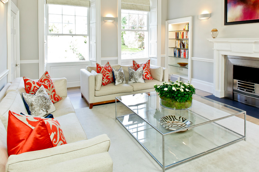 Inspiration for a mid-sized transitional formal and enclosed carpeted living room remodel in Other with gray walls, a standard fireplace and a plaster fireplace