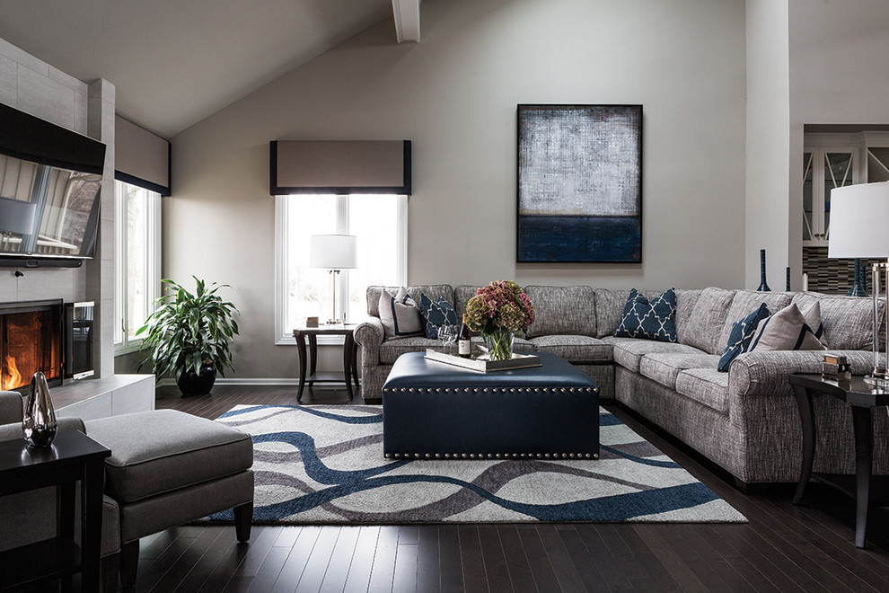 Large transitional formal and open concept dark wood floor living room photo in Kansas City with gray walls, a standard fireplace, a tile fireplace and a wall-mounted tv