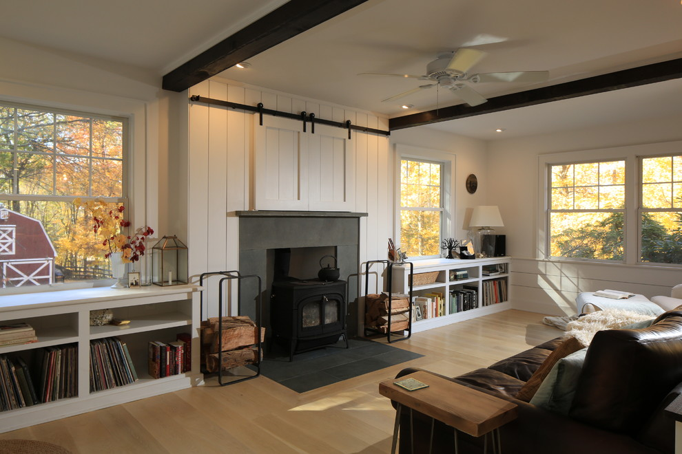 Inspiration for a transitional light wood floor living room remodel in New York with white walls, a wood stove, a stone fireplace and a concealed tv