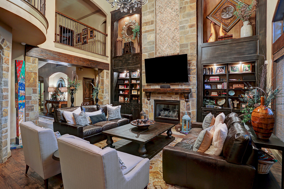 Inspiration for a rustic open concept dark wood floor living room remodel in Houston with beige walls, a standard fireplace, a stone fireplace and a wall-mounted tv