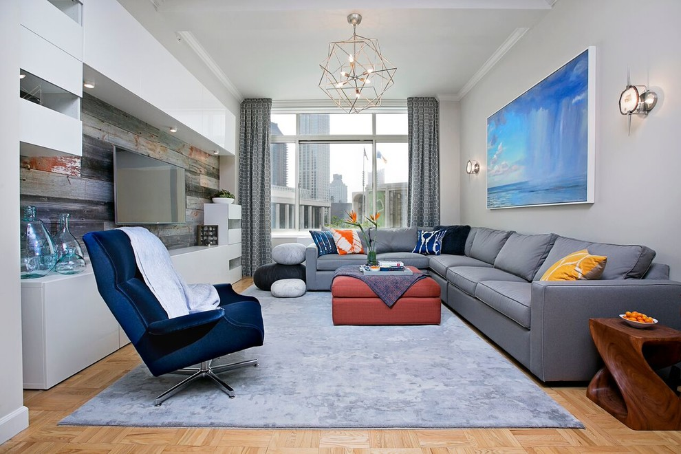 Large trendy open concept light wood floor living room photo in New York with gray walls, no fireplace and a media wall