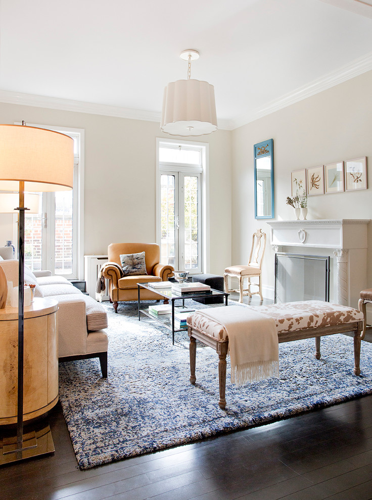 Example of a mid-sized classic formal dark wood floor living room design in New York with beige walls, a standard fireplace, a plaster fireplace and no tv