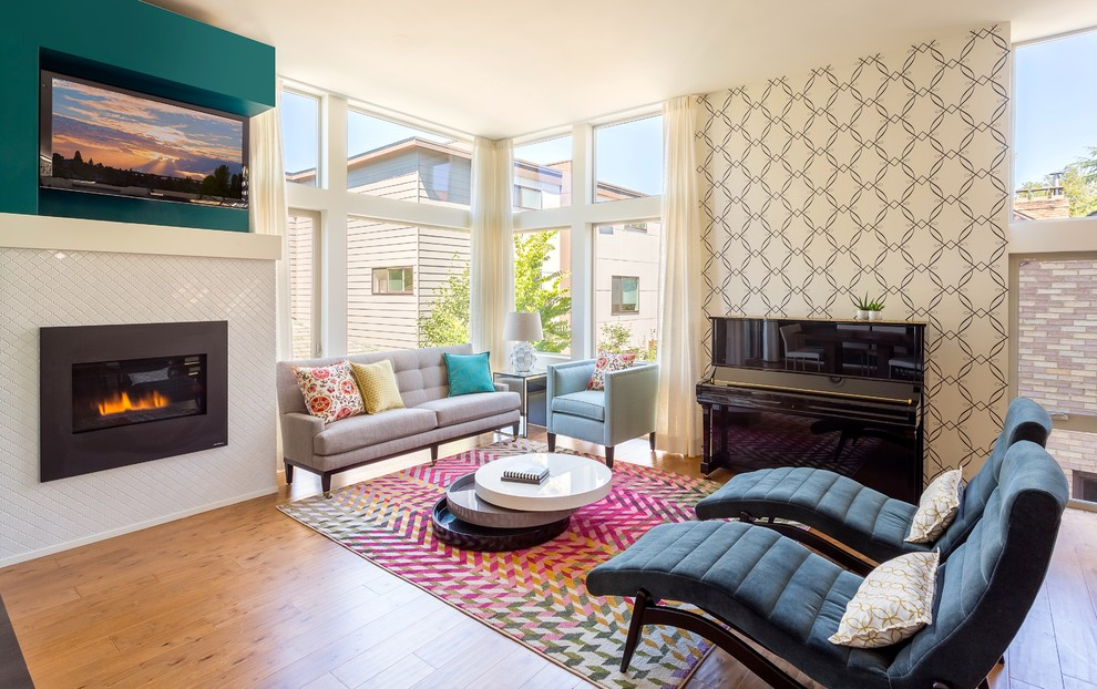 Example of a trendy open concept light wood floor living room design in Seattle with beige walls, a standard fireplace and a wall-mounted tv