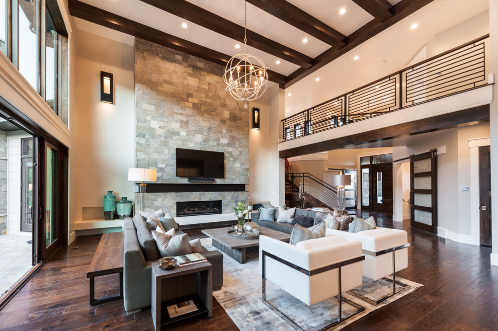 Example of a transitional dark wood floor living room design in Salt Lake City with beige walls, a ribbon fireplace, a stone fireplace and a wall-mounted tv