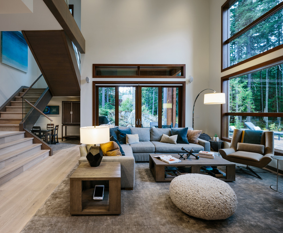 Large trendy open concept medium tone wood floor and gray floor living room photo in Vancouver with white walls