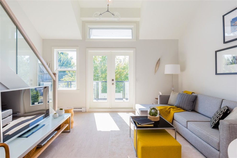 Danish light wood floor and beige floor living room photo in Vancouver with gray walls and a tv stand