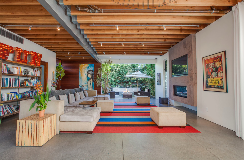 Urban concrete floor living room photo in Los Angeles with white walls and a ribbon fireplace