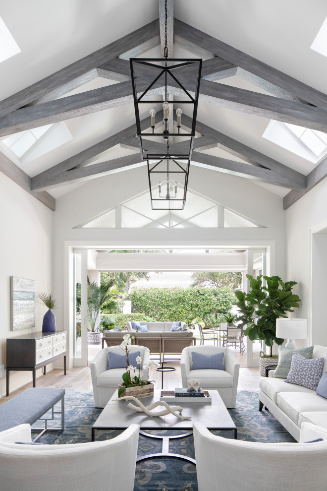 Example of a large beach style open concept light wood floor and beige floor living room design in Miami with gray walls, no fireplace and a wall-mounted tv