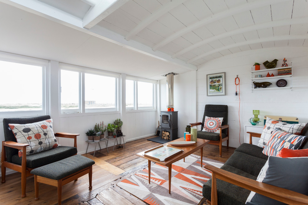Inspiration for a scandinavian medium tone wood floor living room remodel in London with white walls and a wood stove