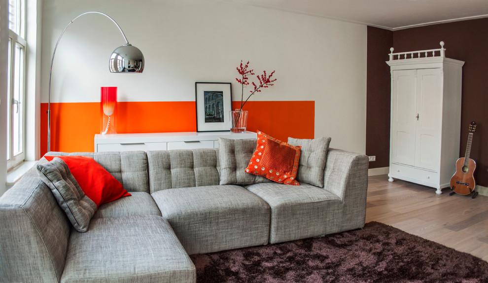 Minimalist beige floor living room photo in Amsterdam with orange walls