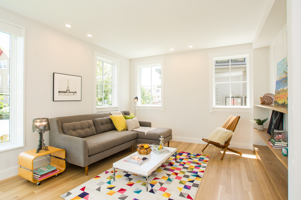 Inspiration for an eclectic enclosed light wood floor and beige floor living room remodel in Boston with white walls and no tv