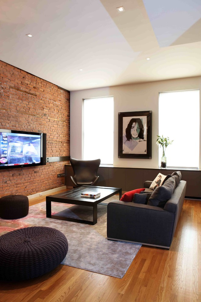 Trendy medium tone wood floor living room photo in New York with a wall-mounted tv