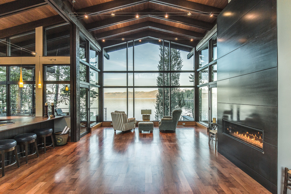 Mountain style open concept medium tone wood floor and brown floor living room photo in Other with a ribbon fireplace