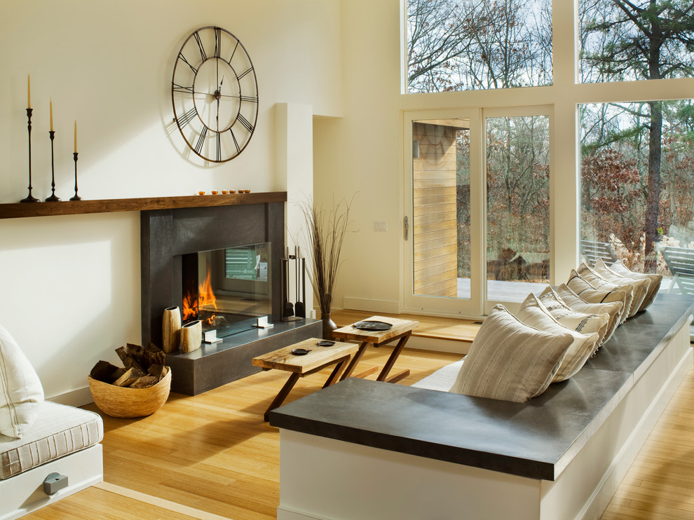 Living room - contemporary living room idea in New York with a concrete fireplace and white walls