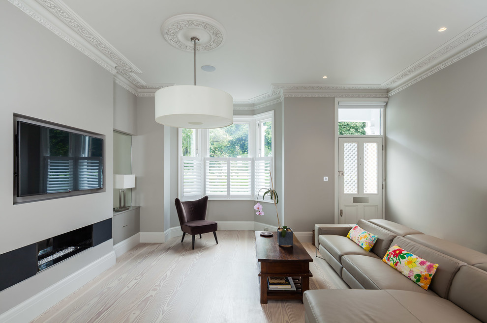 Example of a mid-sized trendy formal light wood floor living room design in London with gray walls, a ribbon fireplace and a wall-mounted tv