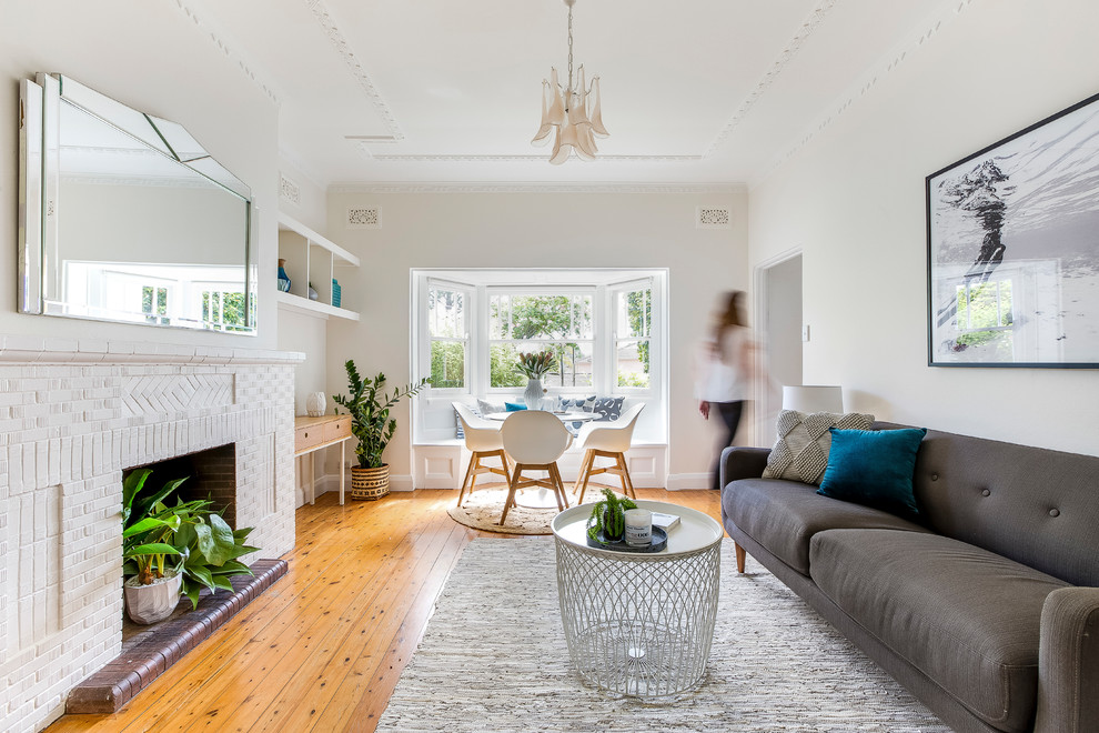Mid-sized danish light wood floor and beige floor living room photo in Sydney with white walls, a two-sided fireplace and a brick fireplace