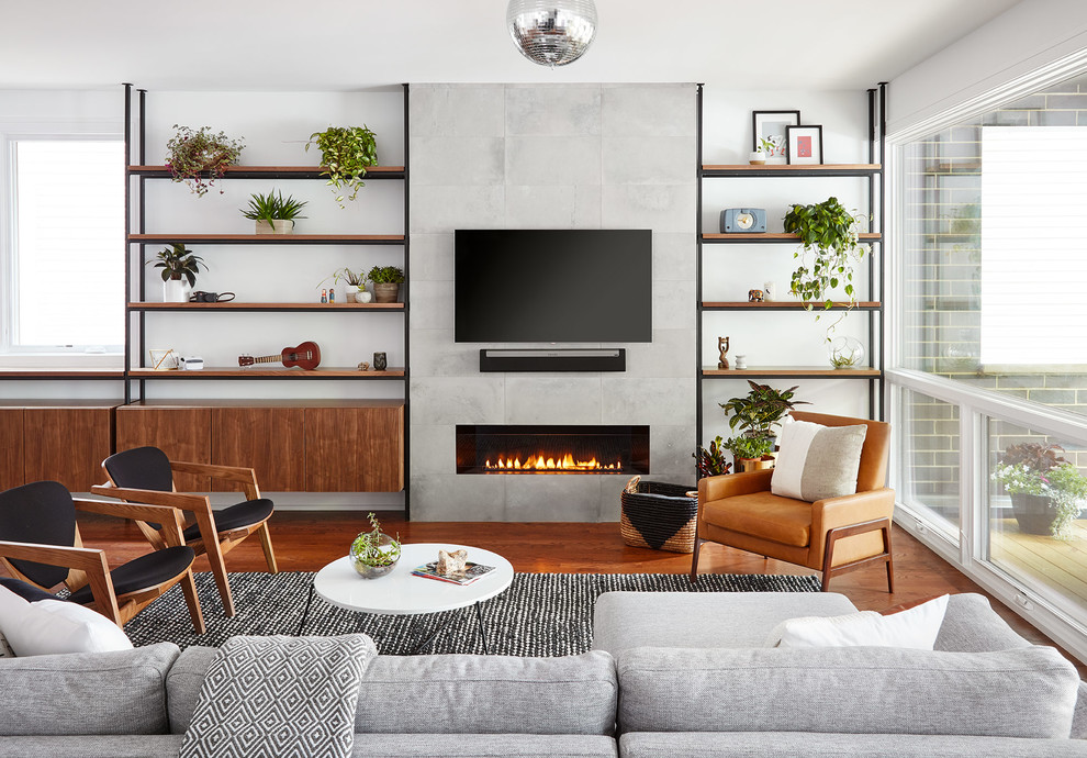 Example of a trendy medium tone wood floor and brown floor living room design in Chicago with white walls, a ribbon fireplace, a tile fireplace and a wall-mounted tv