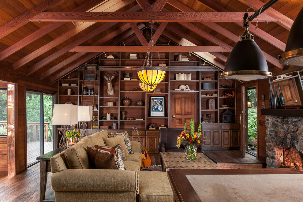 Large mountain style enclosed dark wood floor living room library photo in San Francisco with a standard fireplace and a stone fireplace