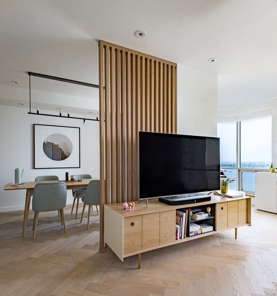 This is an example of a small scandinavian open plan living room in Toronto with white walls, light hardwood flooring and a freestanding tv.