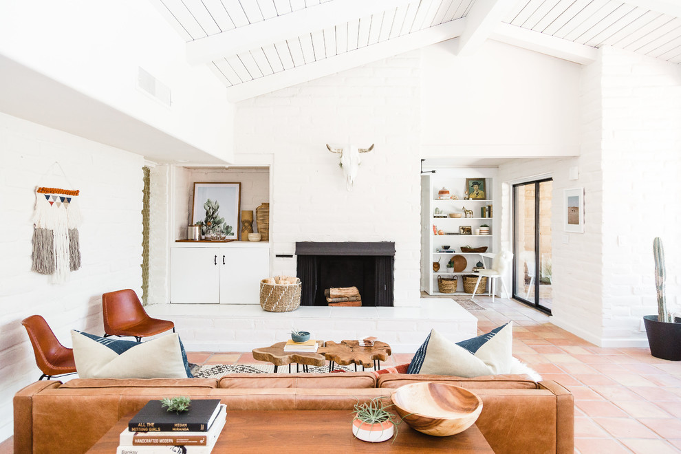 Example of a southwest orange floor living room design in San Diego with white walls, a standard fireplace and a brick fireplace