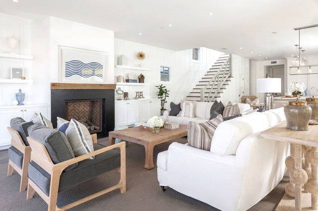 Example of a coastal open concept dark wood floor living room design in Orange County with white walls and a standard fireplace