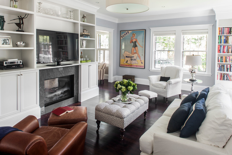 Inspiration for a mid-sized timeless enclosed dark wood floor living room library remodel in Boston with a two-sided fireplace, a stone fireplace, a media wall and gray walls