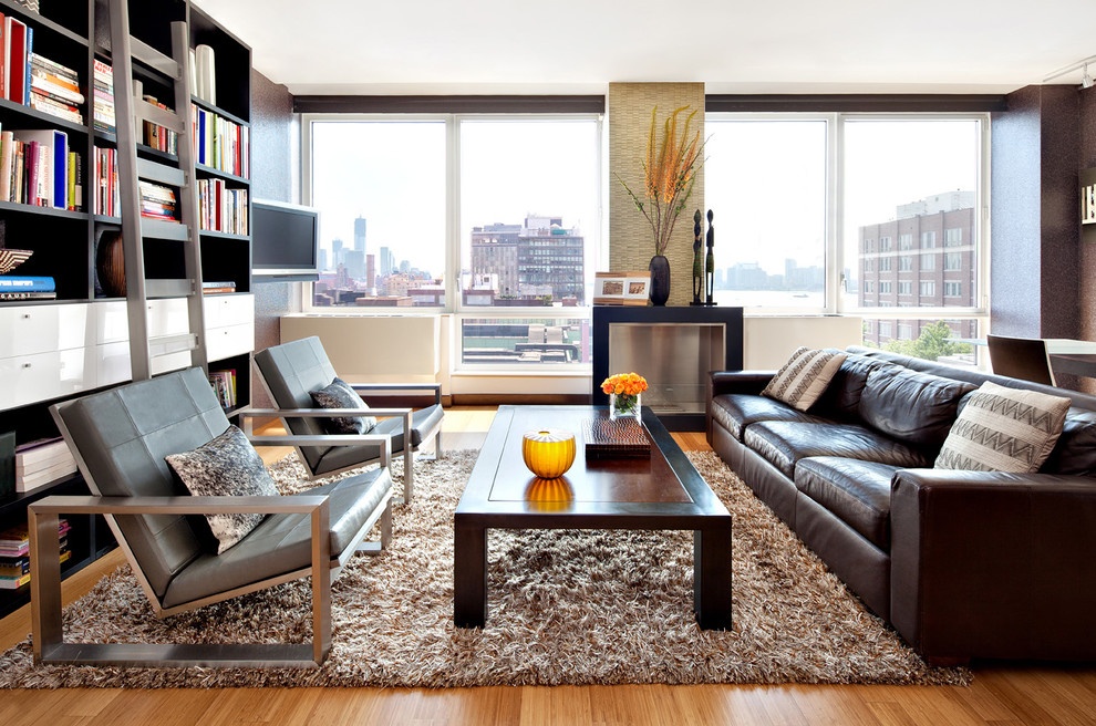 Example of a mid-sized minimalist open concept medium tone wood floor living room library design in New York with gray walls, a standard fireplace, a metal fireplace and a wall-mounted tv