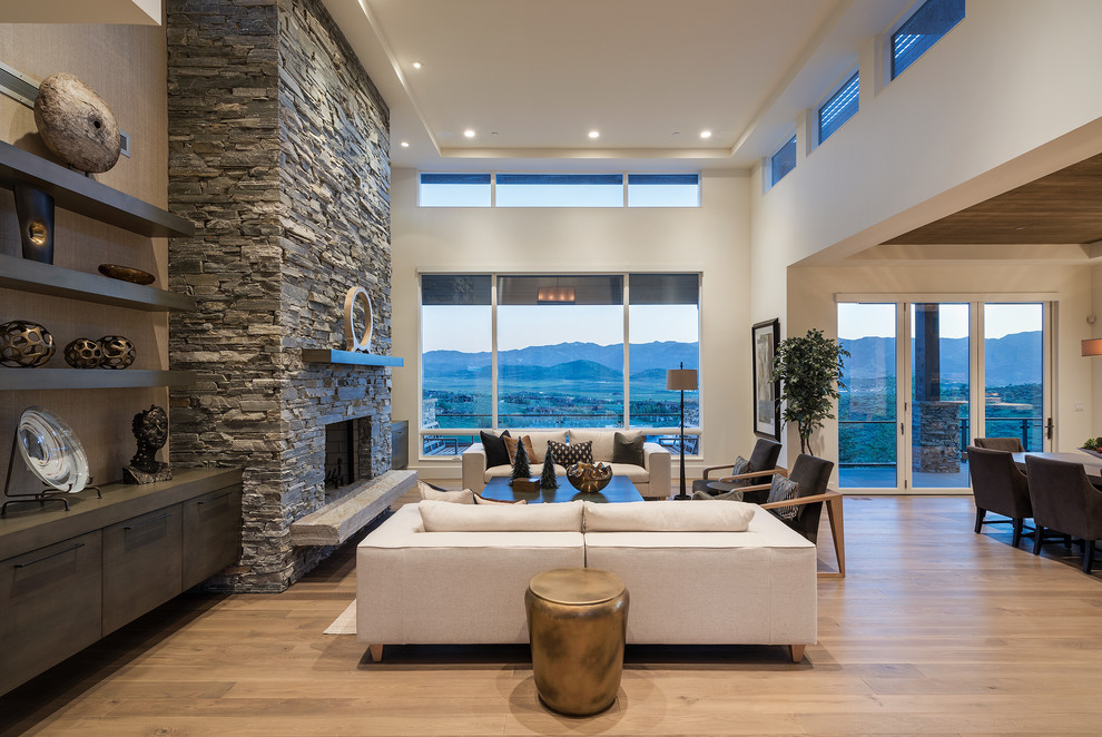 Living room - large contemporary open concept and formal medium tone wood floor living room idea in Salt Lake City with a standard fireplace, a stone fireplace, white walls and no tv