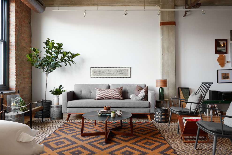 Trendy medium tone wood floor living room photo in Chicago with white walls
