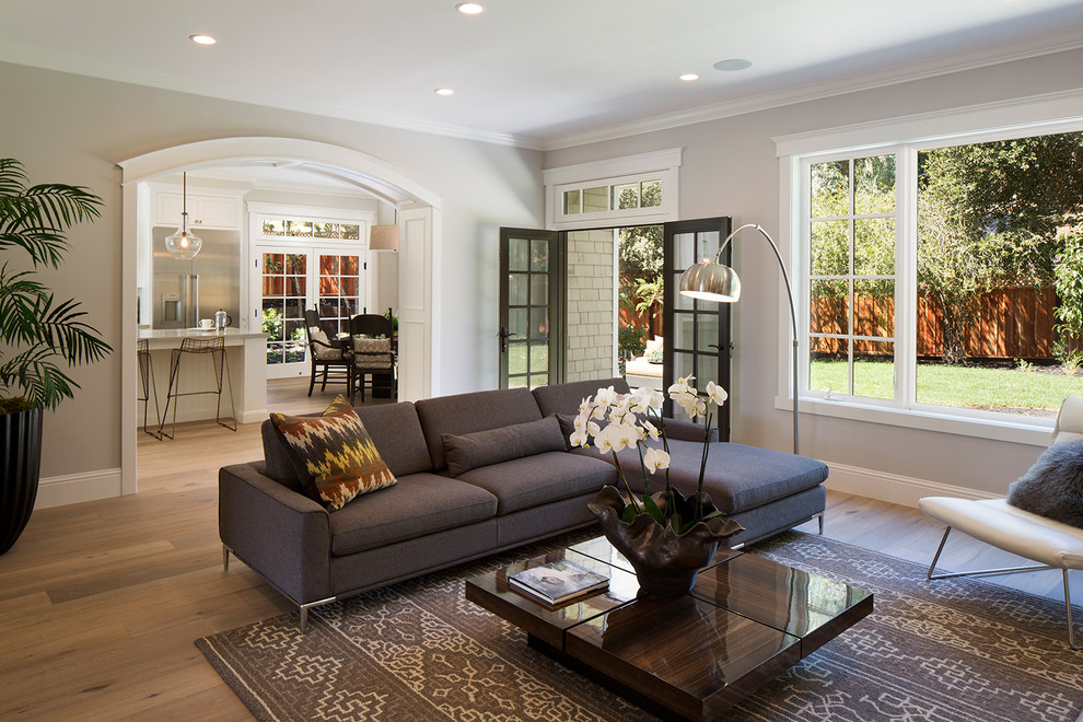 Example of a large transitional open concept light wood floor living room design in San Francisco with gray walls, a standard fireplace, a stone fireplace and a wall-mounted tv